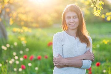 Beautiful young woman with arms crossed standing on a clearing of green grass with blooming tulips
