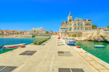 Seafront promenade with iconic Palace Seixas an old and abandoned building, and Praia da Ribeira beach or Praia dos Pescadores on seafront of Cascais, Lisbon Coast in Portugal from pier of Cascais.