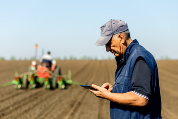 Senior farmer in field examining sowing and holding tablet in his hands.