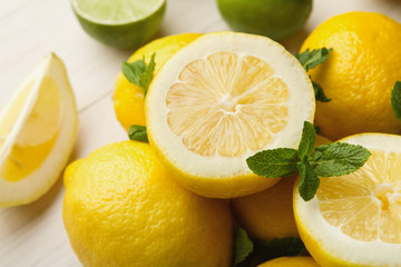 Heap of limes and lemons on white wood
