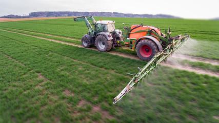 Traktor mit Anhängespritze beim UInkraut spritzen, Luftaufnahme - tilt shift Effekt