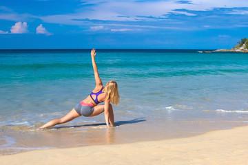 Young woman doing yoga on coast of sea on beach.