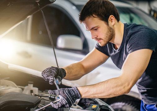 Auto mechanic working under car hood in repair garage