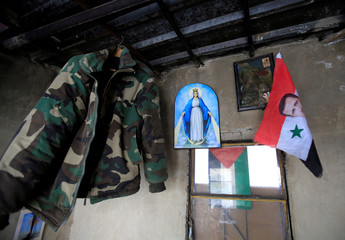 An army jacket, a picture of the Virgin Mary and a Syrian flag with Syria's President Bashar al-Assad are seen in a room in Damascus
