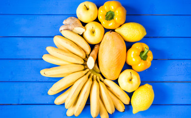 yellow fruits and vegetables isolated on a blue background