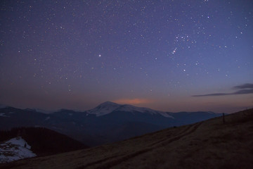 Majestic view of fantastic starry dark sky over magnificent Carpathian mountains covered with evergreen forest and snow-capped peaks in distance. Breathtaking panorama of beauty and magic of nature.