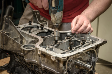 The mechanic repairs the car engine in the workshop, bolts