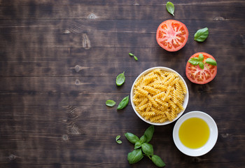 Dark wooden background with pasta, tomato, basil and olive oil