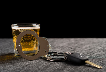 car key and handcuffs in front of cup of beer concept of illegal drunken driving