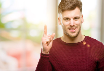 Handsome young man happy and surprised cheering expressing wow gesture pointing up