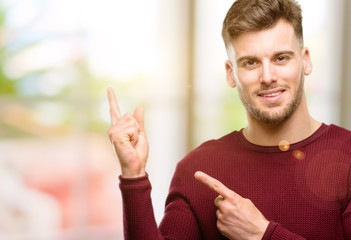Handsome young man pointing away side with fingers
