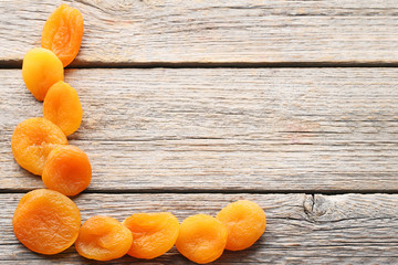 Dried apricots on grey wooden table