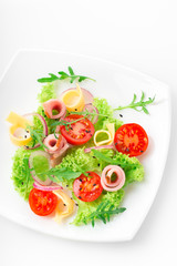Fresh salad with tomatoes, arugula, cheese and ham on the white plate and white background