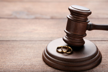 Judge gavel with wedding rings on wooden table