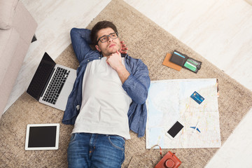Man dreaming about travel, lying on floor