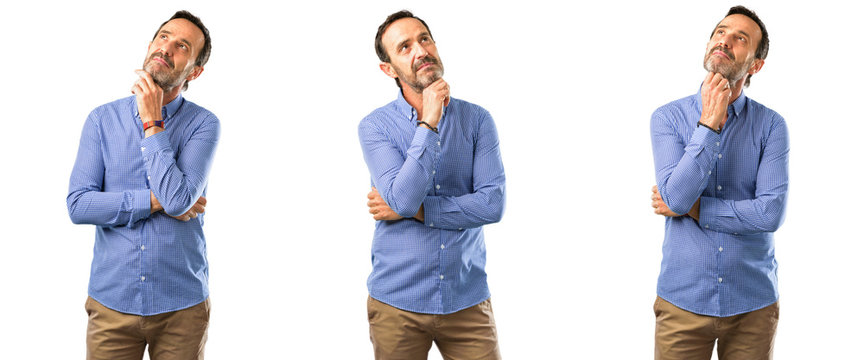 Middle age handsome man thinking and looking up expressing doubt and wonder over white background