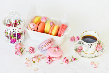 Dessert: A Delicate Fresh Colorful French Macaroons In Pastel Colors With Flowers Roses On A Light Textile Background, Top View