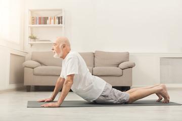 Senior man training yoga in cobra pose indoors