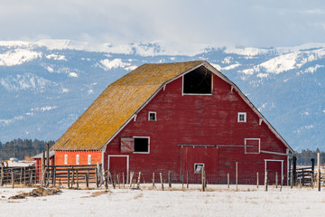 Large classic red barn in winter with tall mountain behind