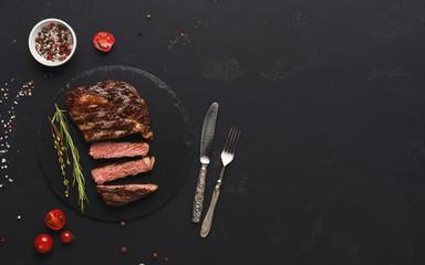 Rib eye steak and spices on black background