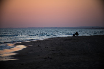 father and son sit near the sea at sunset