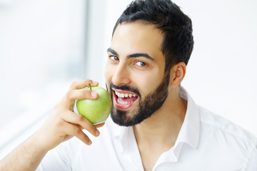 Man Eating Apple. Beautiful Girl With White Teeth Biting Apple. High Resolution Image