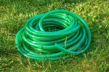 Watering garden hose bundle on the lawn in the garden. Long pvc green garden hose on grass in summer day.
