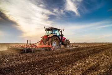 Tractor cultivating field at spring Fotomurales