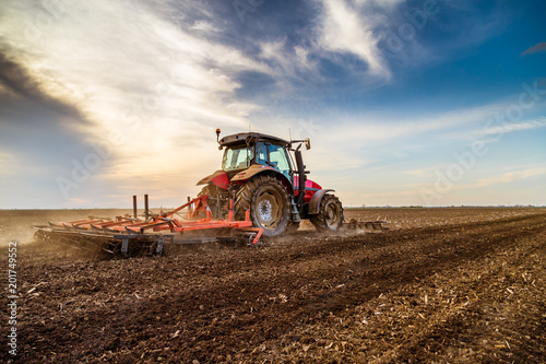 Wall mural Tractor cultivating field at spring