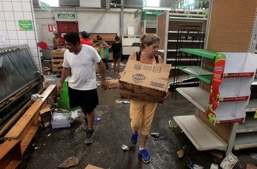 People with goods looted from a store are seen after protests in Managua