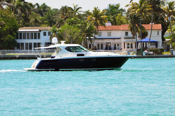 High-end cabin cruiser on the florida intra-coastal waterway with exclusive island homes in the background.