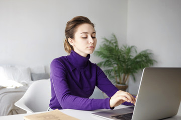 Focused young unemployed woman in turtleneck sitting at her desk in bedroom and keyboarding on generic laptop pc, filling in application form or curriculum vitae, looking for job on internet