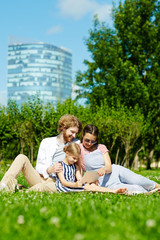 Little girl with touchpad and her parents sitting on green lawn in park and watching movie in the net