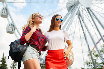 Two friendly girls in casualwear decided to go to one of amusement parks in their city or during travel to another country