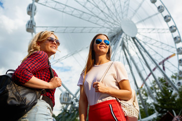 Smiling girls with trendy backpacks looking at theme park through sunglasses on background of ferris wheel