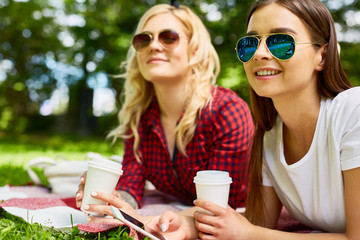Two happy girls in sunglasses having drinks while lying on green lawn in amusements park and watching fun of other people
