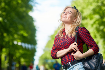 Happy restful girl with backpack looking at one of amusements while taking walk in one of modern theme parks