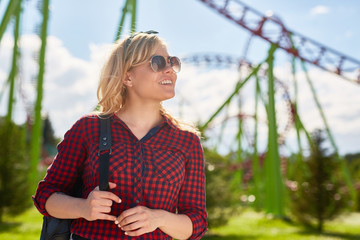 Young pretty blonde deciding what amusement to choose in theme park where she spending weekend or leisure