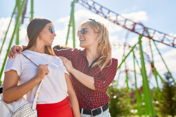 One of young females saying to her friend that they are having nice time in this theme park
