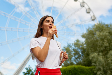 Casual brunette cooling down by tasty icecream in waffle cone in theme park on background of ferris wheel