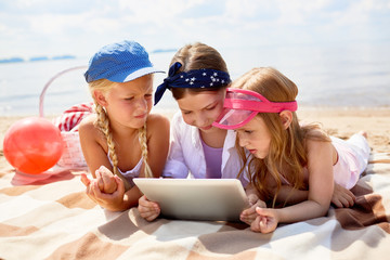 Group of little friendly girls relaxing on beach and watching online video in touchpad