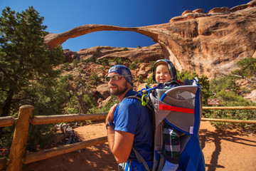 A family with baby son visits Arches National Park in Utah, USA