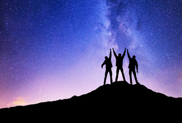 Silhouettes of team on mountain peak. Sport and active life concept on the night sky background.