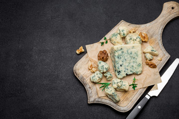 Slice of French Roquefort cheese on wooden board