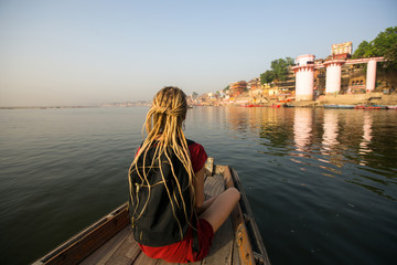 Woman traveler on a boat glides through the water on the Ganges river along the shore of Varanasi, India.