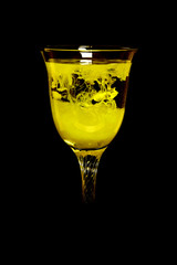 Yellow exotic cocktail in a glass on a black background.
