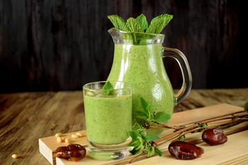 Green smoothie in a glass and in a jug on wooden background