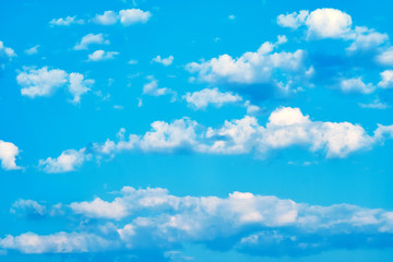 Background of a bright blue sky and blue clouds with sun rays. Bright abstract background ideal for any design. Main background for design