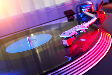 Turntable vinyl record player on the background of a sunset over the lights city. Sound technology for DJ to mix & play music. Black vinyl record. Needle on a vinyl record