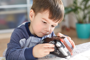 Close up shot of attractive brunet male kid plays with his favourite toy car, tries to repair wheel, has concentrated look, spends free time at home, doesn`t go to kindergarten. Children and leisure